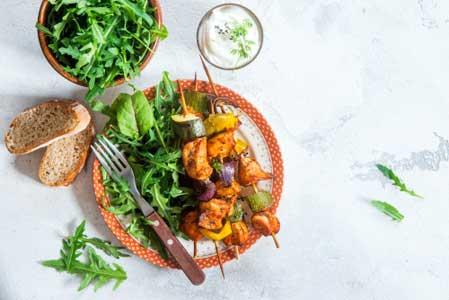 Chicken breast vegetable skewers with arugula salad